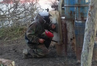 Paintballer at Conflict Paintball hiding behind a oil tank